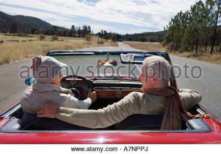 Mature couple sitting in red convertible car on country road woman driving smiling rear view - Stock Photo
