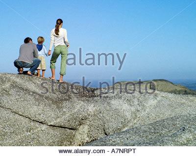 Family standing on rock overlooking Atlantic Ocean looking at horizon rear view - Stock Photo