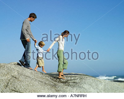 Family walking hand in hand on rocky beach overlooking Atlantic Ocean side view - Stock Photo