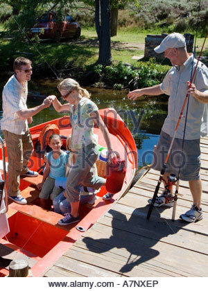 Multi generational family boarding motorboat on lake jetty man offering wife helping hand senior man with fishing - Stock Photo