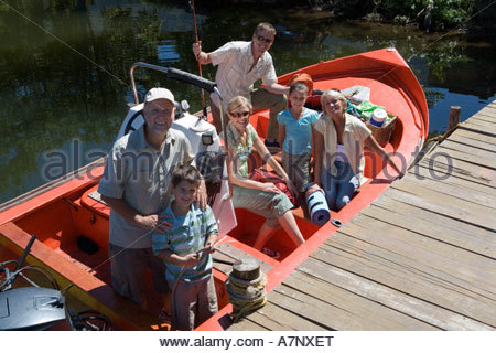 Multi generational family standing in motorboat moored at lake jetty smiling portrait - Stock Photo