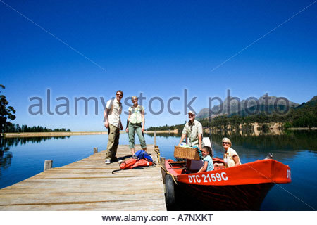 Multi generational family loading motorboat with provisions at lake jetty grandfather holding picnic hamper - Stock Photo