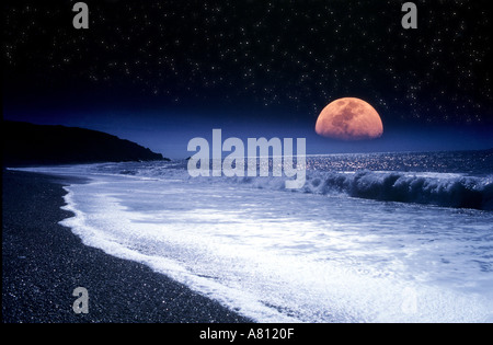 Large moonrise over waves breaking on deserted beach with star lit sky Isle of Wight England - Stock Photo