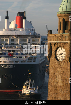Queen Mary II approaching dry dock of Blohm+Voss in Hamburg, Germany, historic clock tower at St. Pauli Landungsbruecken - Stock Photo