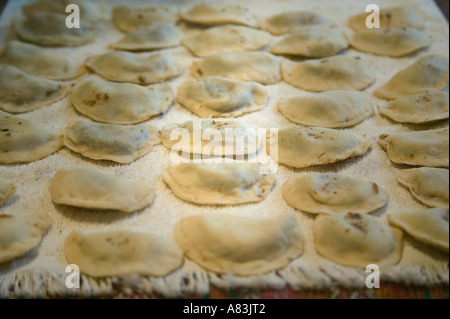 'Warenyky' or 'Pierogie' laid out on a sheet immediately after being rolled. - Stock Photo