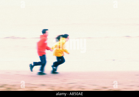 two children running along beach holding hands - Stock Photo