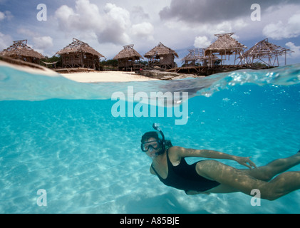 Under over view of woman snorkeling in shallow water Northwest Point Providenciales Provo Turks Caicos Islands - Stock Photo