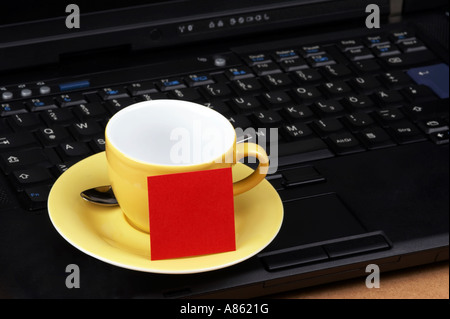 Yellow espresso cup with red post-it on the keyboard of a black laptop - Stock Photo