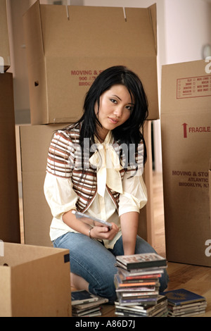 A young woman stacking compact discs - Stock Photo