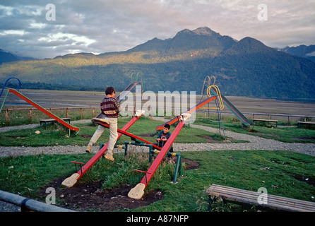 Two Chilean boys on a see saw in a playground in Hornopirén in Patagonia Chile at sunset with mountains in background - Stock Photo
