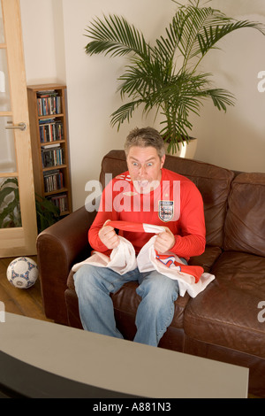 Model released. England football fan sitting at home on sofa watching match on TV excited and happy as team wins. - Stock Photo