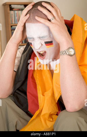 Model released. German football fan sitting on sofa watching TV looking upset as team has just lost. - Stock Photo