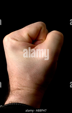 clenched male fist on black bacjground - Stock Photo