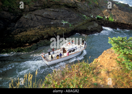 Fishing boat heading to sea between narrow rock channel world s smallest natural navigable harbor Depoe Bay Oregon - Stock Photo