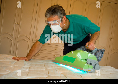 Technician operating specialist UV dust mite vacuum to remove harmful dust mites pests and bed bugs in bedroom - Stock Photo