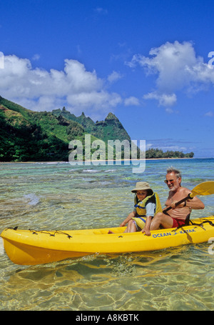 Man and granddaughter in kayak off Tunnels Beach on Kauai - Stock Photo