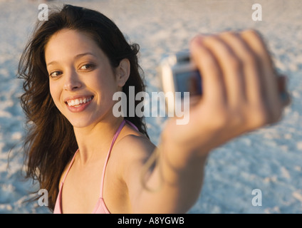Young woman taking photo of self on beach - Stock Photo