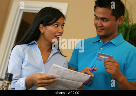 Close-up of a young man cutting a credit card with a pair of scissors - Stock Photo