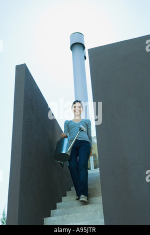 Young woman walking down stairs, carrying watering can - Stock Photo