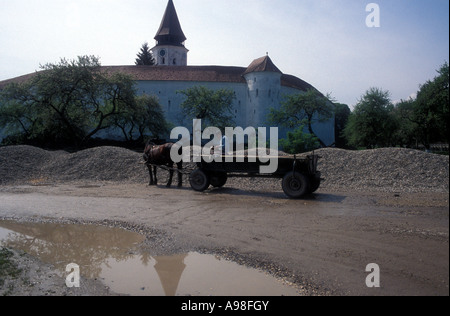 A horse and flat wooden wagon in front of the Saxon fortified church at Prejmer (Transylvania) Romania - Stock Photo
