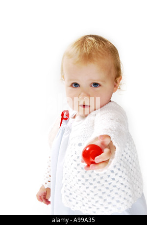 Young girl holding out a red rubber ball - Stock Photo