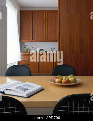 Small apartment with African collection. Dining area with Eames DKR wire base chair with bikini pad. - Stock Photo