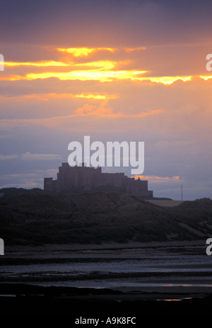SUN GOING DOWN OVER BAMBURGH CASTLE IN NORTHUMBERLAND, ENGLAND, UK - Stock Photo