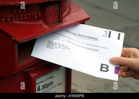 Envelope containing a postal vote being posted into red letterbox England United Kingdom UK - Stock Photo