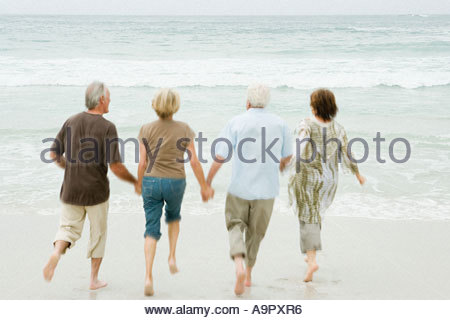Four senior adults running into the sea - Stock Photo