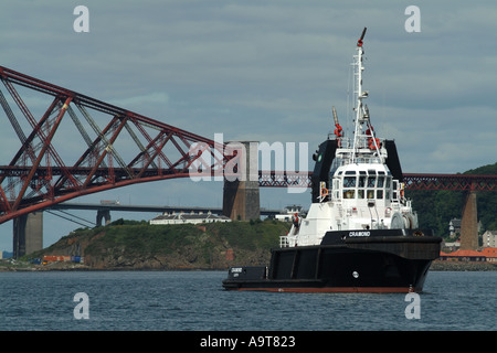 The fire fighting tug Cramond moored in front of the Forth Railway bridge, South Queensferry, Edinburgh, Scotland, - Stock Photo