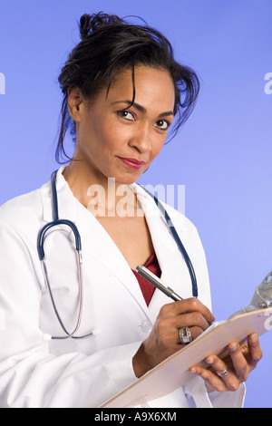 Attractive female doctor writing on a clip board wearing a white coat and stethoscope - Stock Photo