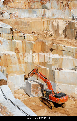 Mechanical shovel excavator is moving a heavy marble stone cuboid in a marble quarry in Colonatta near Carrara, - Stock Photo