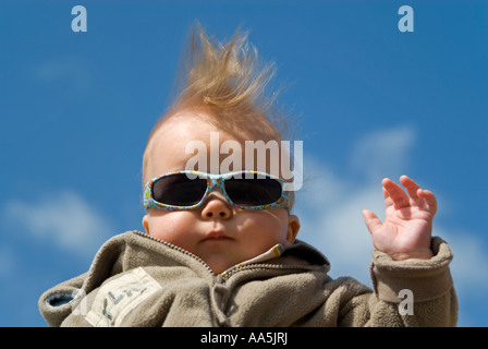 Humorous horizontal close up of a 6-month old baby boy posing for photographs. - Stock Photo
