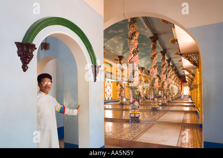 Tay Ninh, Vietnam. A priest stands before the main sanctuary in the Cao Dai Great Temple - Stock Photo