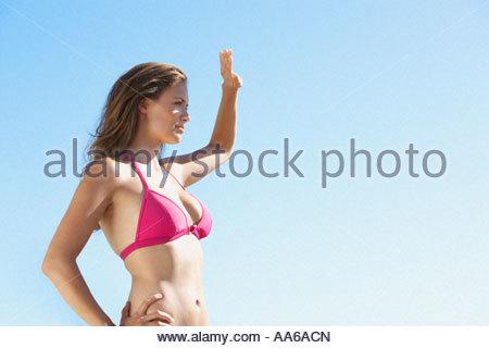 Woman in bikini waist up blocking sun with hand - Stock Photo