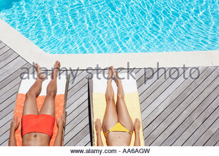 Man and woman sunbathing on pool deck waist down - Stock Photo