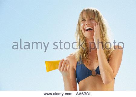 Woman in bikini with sunblock - Stock Photo