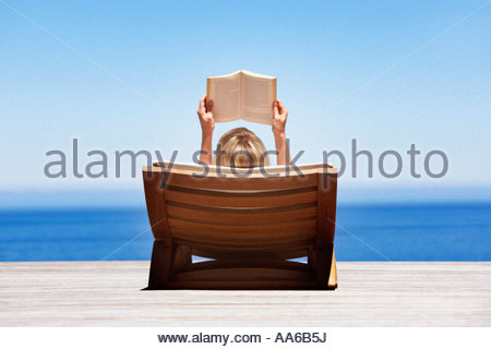 Rear view of woman reading outdoors in wooden chair - Stock Photo