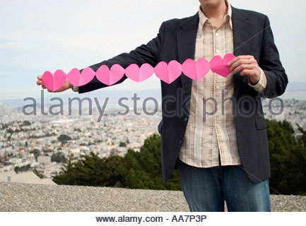 Man holding paper heart chain - Stock Photo