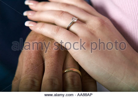 Couple wearing wedding rings holding hands - Stock Photo