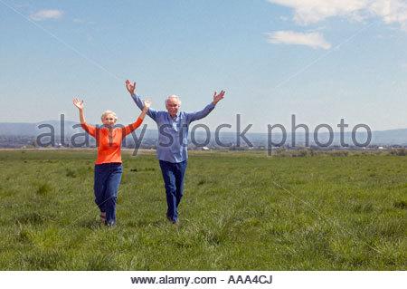 Senior couple running through fields - Stock Photo