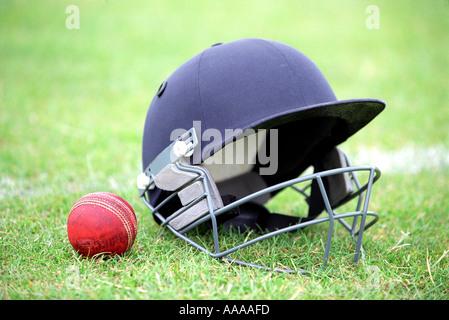 A cricket helmet and ball - Stock Photo