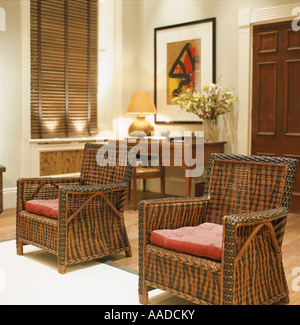Matching patterned wicker armchairs with red cushions - Stock Photo