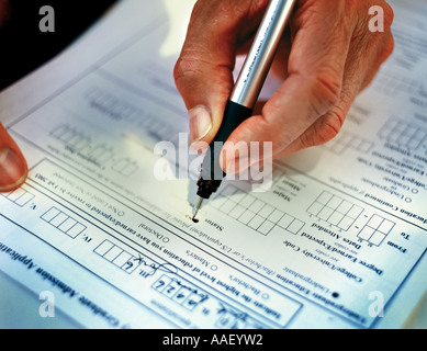 close-up of hand holding pen filling out information - Stock Photo