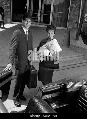 1960s COUPLE TAKING NEW BABY HOME FROM HOSPITAL FATHER HOLDING CONVERTIBLE CAR DOOR OPEN FOR MOTHER - Stock Photo
