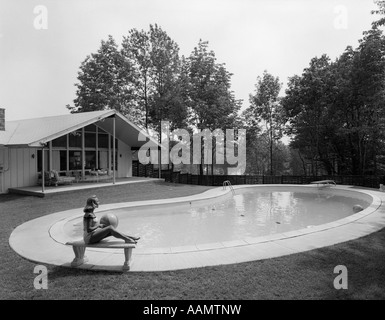 1950s 1960s BLOND WOMAN BATHING SUIT SITTING ON STONE BENCH BEACH BALL NEAR KIDNEY SHAPED SWIMMING POOL - Stock Photo