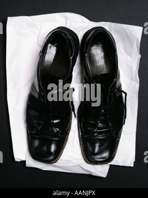 Dead man's shoes on black background - Stock Photo