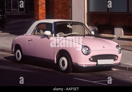 Nissan Figaro: Pink version of this 2 door canvas sun roof retro fashion car (1991) parked on a street in Covent - Stock Photo