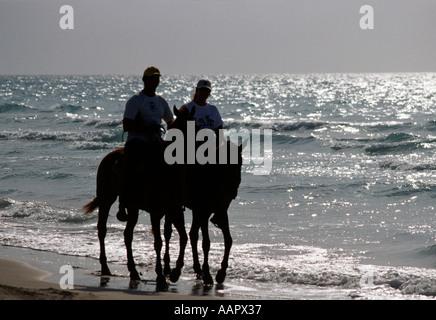 Couple riding horses along the shore at Jibacoa beach Cuba - Stock Photo