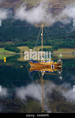 Lovely traditionally built wooden sailing boat moored on Loch Leven near Ballachulish Glencoe with light clouds - Stock Photo
